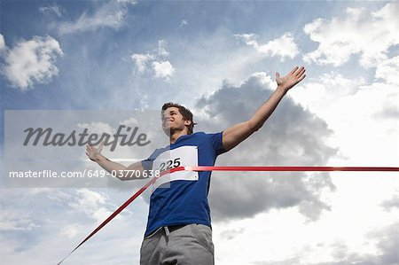 Young man crossing finish line Stock Photo - Premium Royalty-Free, Image code: 649-03770638