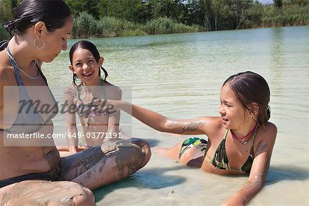 Family playing together in a muddy lake Stock Photo - Premium Royalty-Free, Image code: 649-03771191