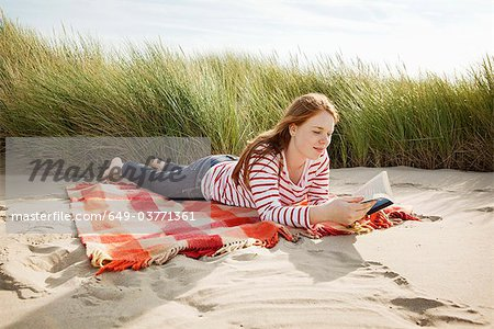 Teenager reading book in sand dunes Stock Photo - Premium Royalty-Free, Image code: 649-03771361