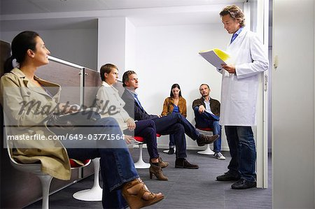 Doctor calling a patient in waiting room Stock Photo - Premium Royalty-Free, Image code: 649-03771564