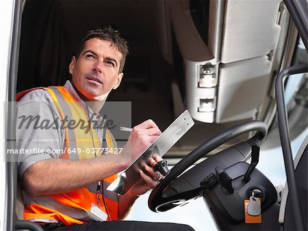 Truck driver makes notes in truck cab Stock Photo - Premium Royalty-Free, Image code: 649-03773427