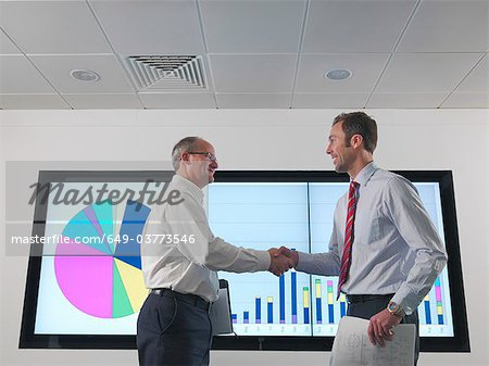 Businessmen shake hands with screen Stock Photo - Premium Royalty-Free, Image code: 649-03773546