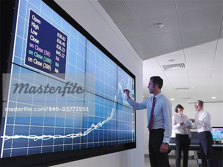 Businessman using graphs on screen Stock Photo - Premium Royalty-Free, Image code: 649-03773551
