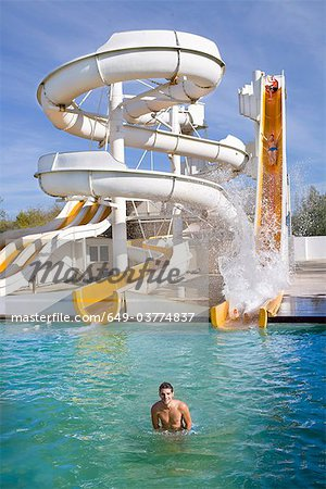 Man smiles in water at giant water slide Stock Photo - Premium Royalty-Free, Image code: 649-03774837