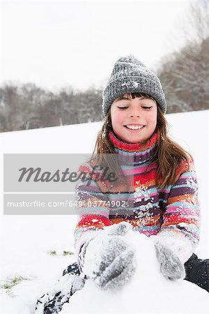 Girl building snowman Stock Photo - Premium Royalty-Free, Image code: 649-03774902