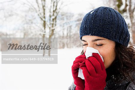 Woman wiping her nose Stock Photo - Premium Royalty-Free, Image code: 649-03774919