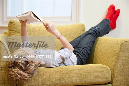 Young boy reading in an armchair Stock Photo - Premium Royalty-Free, Image code: 649-03774992