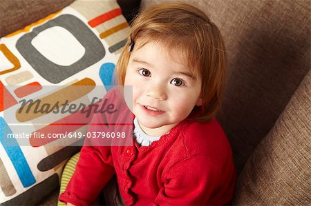 Young girl sitting on sofa looking up Stock Photo - Premium Royalty-Free, Image code: 649-03796098