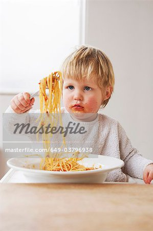 Messy baby boy eating spaghetti Stock Photo - Premium Royalty-Free, Image code: 649-03796938