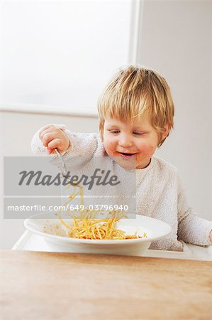 Happy baby boy eating spaghetti Stock Photo - Premium Royalty-Free, Image code: 649-03796940
