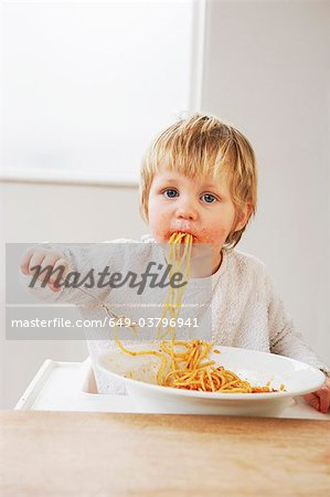 Messy baby boy eating spaghetti Stock Photo - Premium Royalty-Free, Image code: 649-03796941