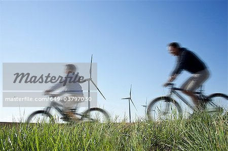 Father and son cycling past a windfarm Stock Photo - Premium Royalty-Free, Image code: 649-03797030