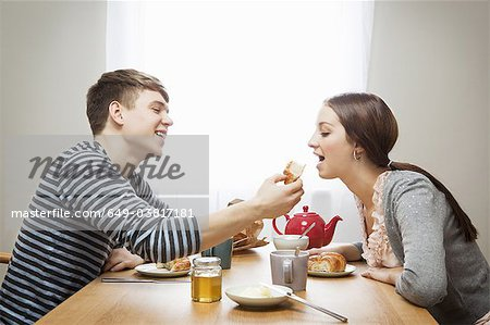 Man feeds girlfriend croissant at table Stock Photo - Premium Royalty-Free, Image code: 649-03817181