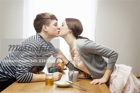 Woman kissing boyfriend over table Stock Photo - Premium Royalty-Free, Image code: 649-03817182
