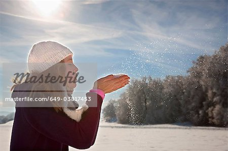 Woman blowing snow from hands Stock Photo - Premium Royalty-Free, Image code: 649-03817453