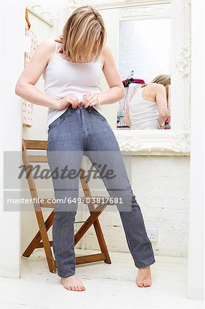 Woman trying on jeans Stock Photo - Premium Royalty-Free, Image code: 649-03817681