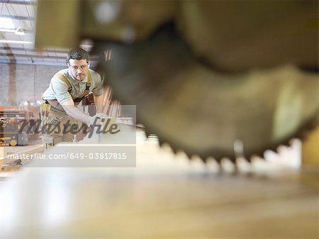 Woodworker sawing timber Stock Photo - Premium Royalty-Free, Image code: 649-03817815