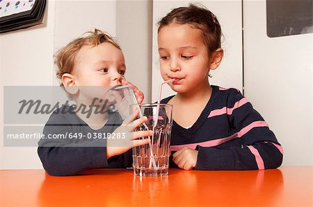 Boy and girl drinking water with straws Stock Photo - Premium Royalty-Free, Image code: 649-03818283