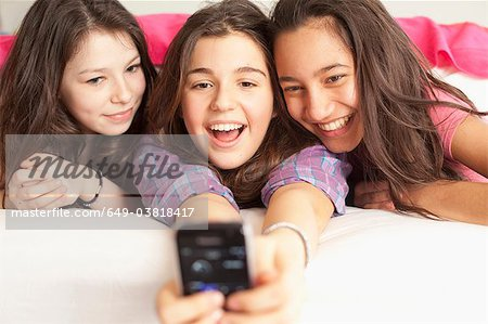 teenage girls taking photos wearing pajamas Stock Photo - Premium Royalty-Free, Image code: 649-03818417