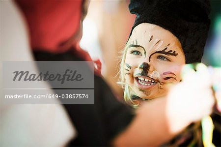 Girl wearing face paint at carnival Stock Photo - Premium Royalty-Free, Image code: 649-03857574