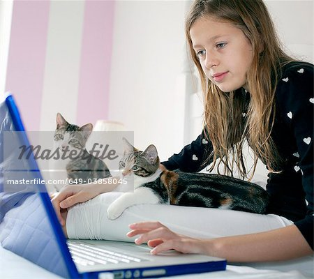 Girl using laptop with kittens Stock Photo - Premium Royalty-Free, Image code: 649-03858045