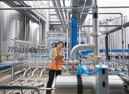 Worker with machinery in bottling plant Stock Photo - Premium Royalty-Free, Image code: 649-03858242