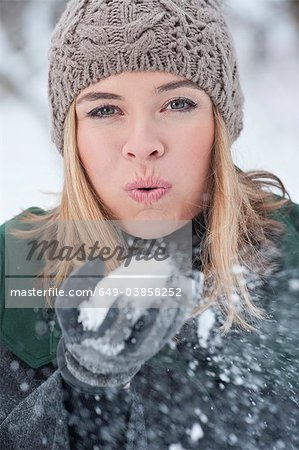 Woman blowing handful of snow Stock Photo - Premium Royalty-Free, Image code: 649-03858252