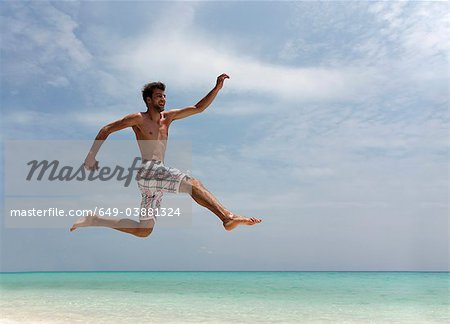 Man jumping on tropical beach Stock Photo - Premium Royalty-Free, Image code: 649-03881324