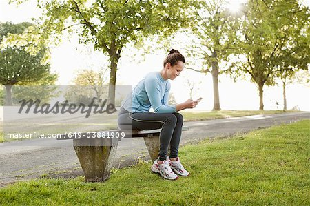 Runner using cell phone in park Stock Photo - Premium Royalty-Free, Image code: 649-03881909