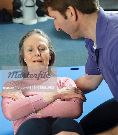 Trainer helping older woman exercise Stock Photo - Premium Royalty-Free, Image code: 649-03881958