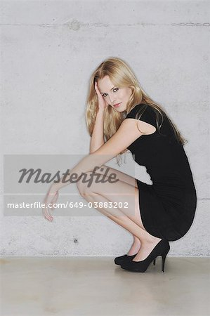 Woman crouching in short black dress Stock Photo - Premium Royalty-Free, Image code: 649-03883202