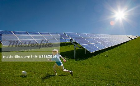 Boy playing in field by solar panels