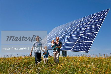 Family walking in field by solar panel Stock Photo - Premium Royalty-Free, Image code: 649-03883521