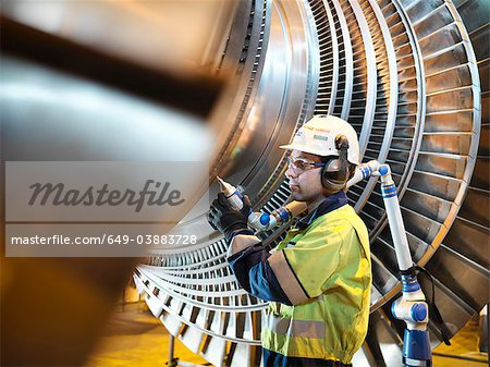 Worker inspects turbine in power station Stock Photo - Premium Royalty-Free, Image code: 649-03883728