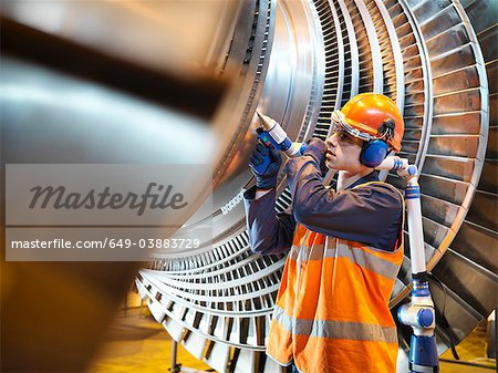 Worker inspects turbine in power station Stock Photo - Premium Royalty-Free, Image code: 649-03883729
