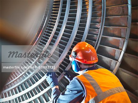 Worker inspects turbine in power station Stock Photo - Premium Royalty-Free, Image code: 649-03883731