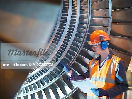 Worker inspects turbine in power station Stock Photo - Premium Royalty-Free, Image code: 649-03883732