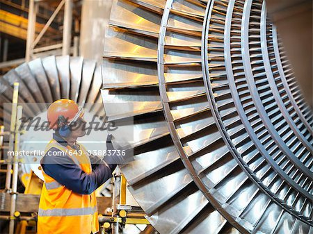 Worker inspects turbine in power station Stock Photo - Premium Royalty-Free, Image code: 649-03883736