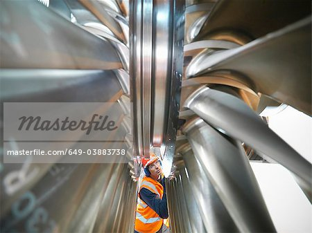 Worker inspects turbine in power station Stock Photo - Premium Royalty-Free, Image code: 649-03883738