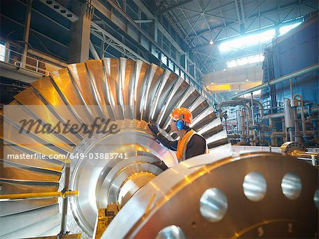Worker inspects turbine in power station Stock Photo - Premium Royalty-Free, Image code: 649-03883741