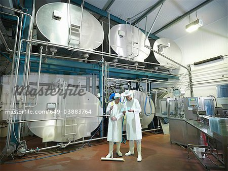 Workers inspecting goat yogurt in dairy Stock Photo - Premium Royalty-Free, Image code: 649-03883764