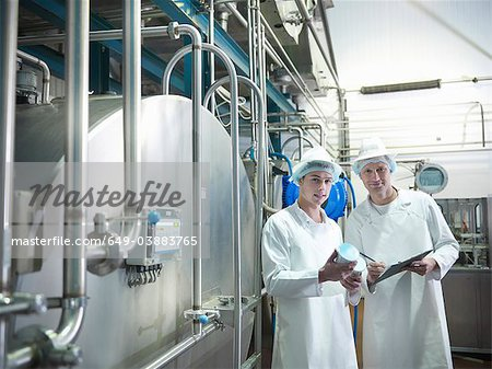 Workers inspecting goat yogurt in dairy Stock Photo - Premium Royalty-Free, Image code: 649-03883765