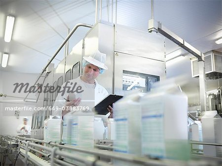 Worker inspecting goat's milk in dairy Stock Photo - Premium Royalty-Free, Image code: 649-03883769