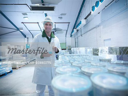 Worker with yogurt in dairy cold store Stock Photo - Premium Royalty-Free, Image code: 649-03883775