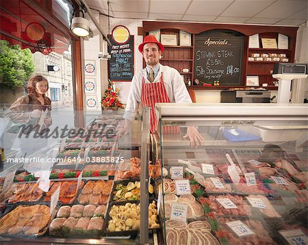 Butcher standing behind counter in shop Stock Photo - Premium Royalty-Free, Image code: 649-03883825
