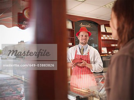 Butcher showing meat to customer Stock Photo - Premium Royalty-Free, Image code: 649-03883826