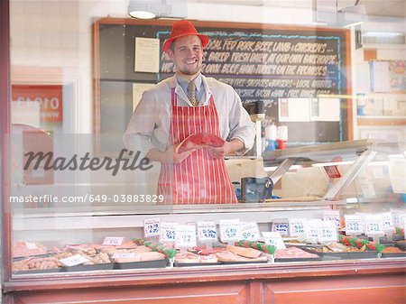Butcher holding steak behind counter Stock Photo - Premium Royalty-Free, Image code: 649-03883829