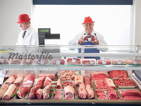 Butcher standing behind meat counter Stock Photo - Premium Royalty-Free, Image code: 649-03883831