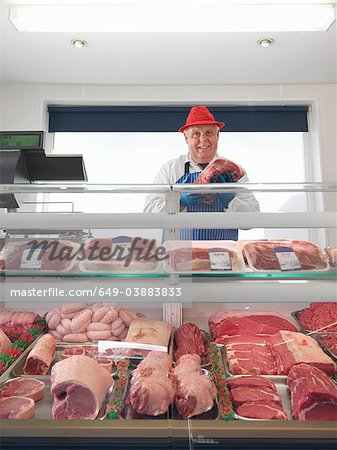 Butcher standing behind meat counter Stock Photo - Premium Royalty-Free, Image code: 649-03883833