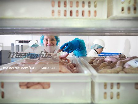 Worker inspecting sausages in factory Stock Photo - Premium Royalty-Free, Image code: 649-03883841